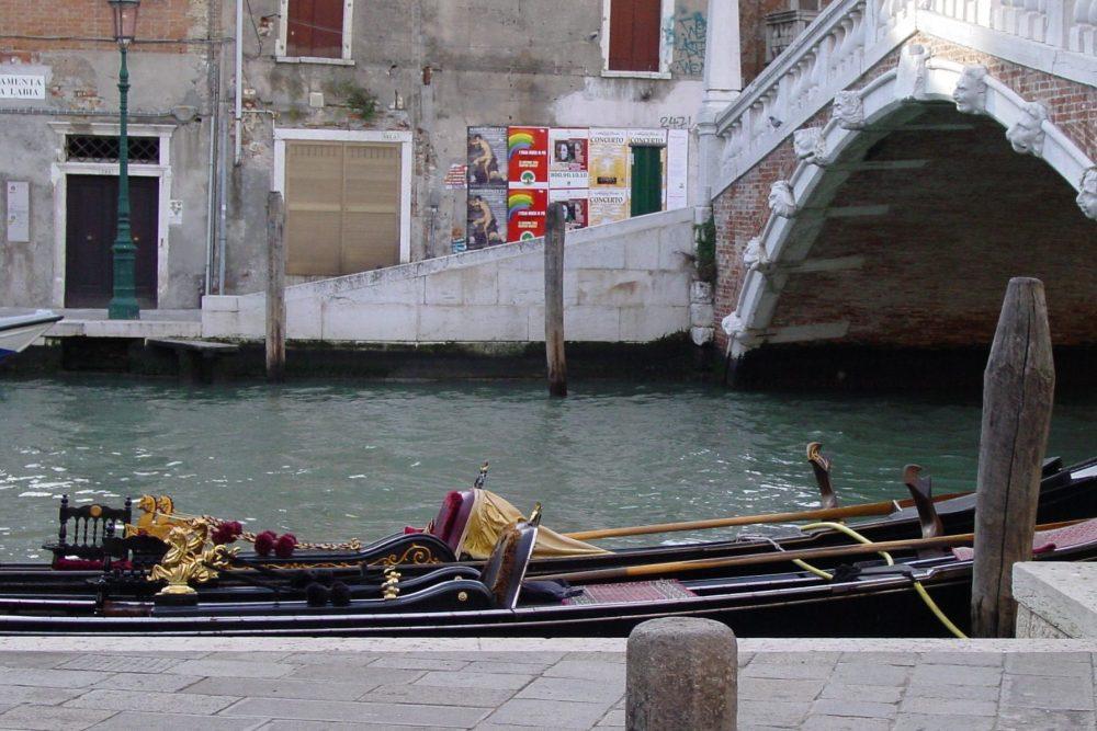 Zu sehen ist eine Gondel in Venedig an einem kleinen Kanal.